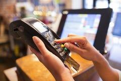 Mano de la mujer con el golpe fuerte de la tarjeta de crédito a través del terminal para la venta
