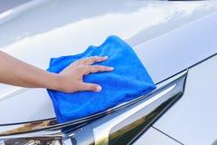 Mano de la mujer con el paño azul de la microfibra que limpia el coche Imagen de archivo