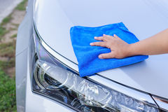 Mano de la mujer con el paño azul de la microfibra que limpia el coche Imagen de archivo libre de regalías