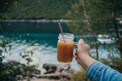 Mano de la mujer con el zumo de naranja de la vitamina en un tarro de cristal en el backg Imagen de archivo libre de regalías