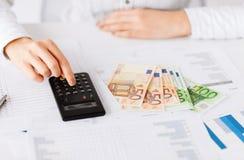 Mano de la mujer con la calculadora y el dinero del euro Imagen de archivo