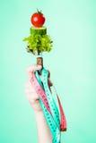 Mano de la mujer con la comida y las cintas métricas vegetarianas Foto de archivo libre de regalías