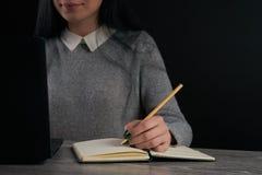 Mano de la mujer con la escritura del lápiz en el cuaderno Fotografía de archivo