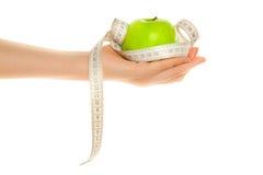 Mano de la mujer con la manzana verde y la cinta métrica Imagen de archivo libre de regalías