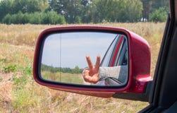 Mano de la mujer con la muestra de la paz en el mirr del foco del espejo de la visión Imágenes de archivo libres de regalías