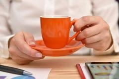 Mano de la mujer con la taza de café foto de archivo