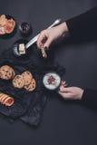 Mano de la mujer con la taza de las galletas del café o del capuchino y del chocolate, galletas en fondo negro de la tabla Tiempo Imagen de archivo
