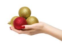 Mano de la mujer con las bolas del Año Nuevo Fotos de archivo