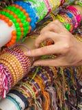Mano de la mujer con las pulseras coloridas en parada en el bazar Imagen de archivo libre de regalías