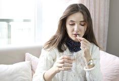 Mano de la mujer con las tabletas de la medicina de las píldoras y el vidrio de agua en sus manos foto de archivo