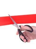 Mano de la mujer con las tijeras que cortan la cinta roja Foto de archivo