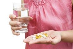 Mano de la mujer con las vitaminas y los suplementos Fotografía de archivo