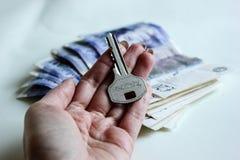 Mano de la mujer con llave de la casa en un fondo del rollo del dinero de veinte libras fotografía de archivo libre de regalías