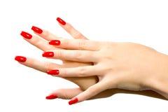 Mano de la mujer con los clavos rojos Fotos de archivo libres de regalías