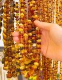 Mano de la mujer con los collares ambarinos femeninos brillantes en parada en el bazar Fotografía de archivo libre de regalías