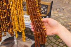 Mano de la mujer con los collares ambarinos femeninos brillantes en parada en el bazar Imagen de archivo