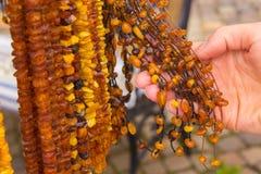 Mano de la mujer con los collares ambarinos femeninos brillantes en parada en el bazar Imagenes de archivo