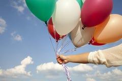 Mano de la mujer con los globos coloridos Imagenes de archivo