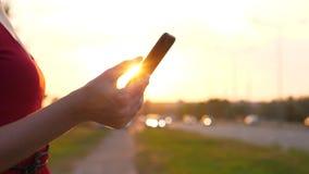 Mano de la mujer con smartphone contra el camino con la conducción de los coches almacen de video