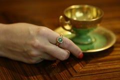 Mano de la mujer con un anillo y una taza esmeralda antiguos del mocca imagen de archivo