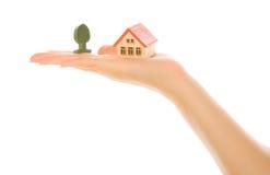 Mano de la mujer con una pequeña casa Foto de archivo
