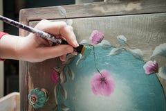Mano de la mujer con una pintura del cepillo con el aparador de madera de la pintura cretácea Imagen de archivo libre de regalías