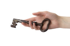 Mano de la mujer con vieja llave en el fondo blanco Foto de archivo