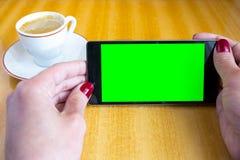 Mano de la mujer de la pantalla del verde de Smartphone Foto de archivo