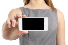 Mano de la mujer de negocios que exhibe una pantalla elegante en blanco del teléfono Imagen de archivo