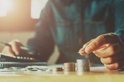 Mano de la mujer del dinero del ahorro que pone fina del negocio del concepto de la pila de la moneda fotos de archivo