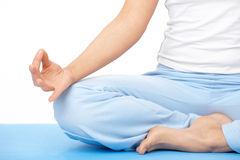 Mano de la mujer del primer que hace ejercicio de la yoga en la estera imagen de archivo