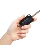 Mano de la mujer en el fondo aislado que lleva a cabo clave del coche Foto de archivo libre de regalías