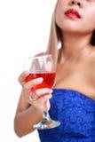 Mano de la mujer en el vestido azul que sostiene el vino rojo fotos de archivo
