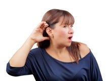 Mano de la mujer en escuchar del oído sorprendido aislado Imagen de archivo