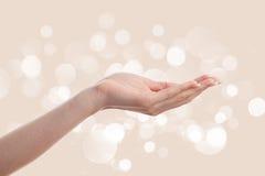 Mano de la mujer en fondo marrón Imagen de archivo libre de regalías