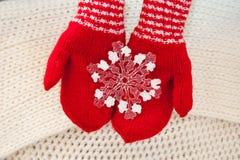 Mano de la mujer en los guantes rojos que sostienen el copo de nieve grande blanco Foto de archivo libre de regalías