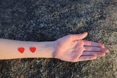 Mano de la mujer joven con dos pequeños corazones rojos imágenes de archivo libres de regalías