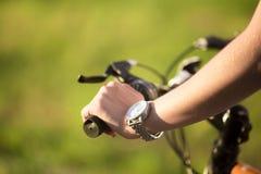 Mano de la mujer joven en la manija de la bici Imagen de archivo