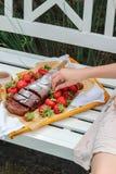 Mano de la mujer joven que alcanza para una bandeja con la torta hecha en casa y las fresas frescas imagenes de archivo