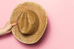 Mano de la mujer joven que sostiene el sombrero de paja del verano en fondo rosado Foto de archivo libre de regalías