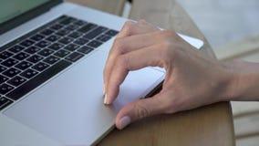 Mano de la mujer joven que usa el panel táctil del ordenador portátil mientras que trabaja almacen de video