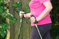 Mano de la mujer mayor mayor con los bastones nórdicos, formas de vida deportivas en concepto de la edad avanzada Fotos de archivo