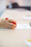 Mano de la mujer mayor con Pen On Desk Foto de archivo libre de regalías