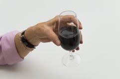 Mano de la mujer mayor que sostiene un vidrio de vino rojo Fotos de archivo libres de regalías