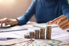 mano de la mujer de negocios que sostiene monedas para apilar en finanzas de ahorro del dinero del concepto del escritorio fotos de archivo