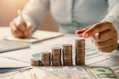 mano de la mujer de negocios que sostiene monedas para apilar en finanzas de ahorro del dinero del concepto del escritorio fotografía de archivo libre de regalías