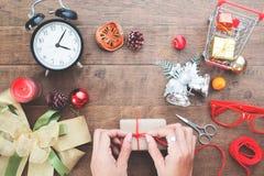 Mano de la mujer que adorna la caja de regalo con los ornamentos de la Navidad en de madera Imagen de archivo libre de regalías