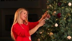 Mano de la mujer que adorna el árbol de navidad con las luces del resplandor de la Navidad almacen de video