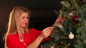 Mano de la mujer que adorna el árbol de navidad con las luces del resplandor de la Navidad almacen de metraje de vídeo