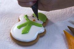 Mano de la mujer que adorna el pan de jengibre bajo la forma de un muñeco de nieve con el azúcar de formación de hielo usando un  Fotos de archivo libres de regalías